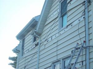 Rows of siding removed and holes were insulation was blown in between studs. Later the original siding was replaced.