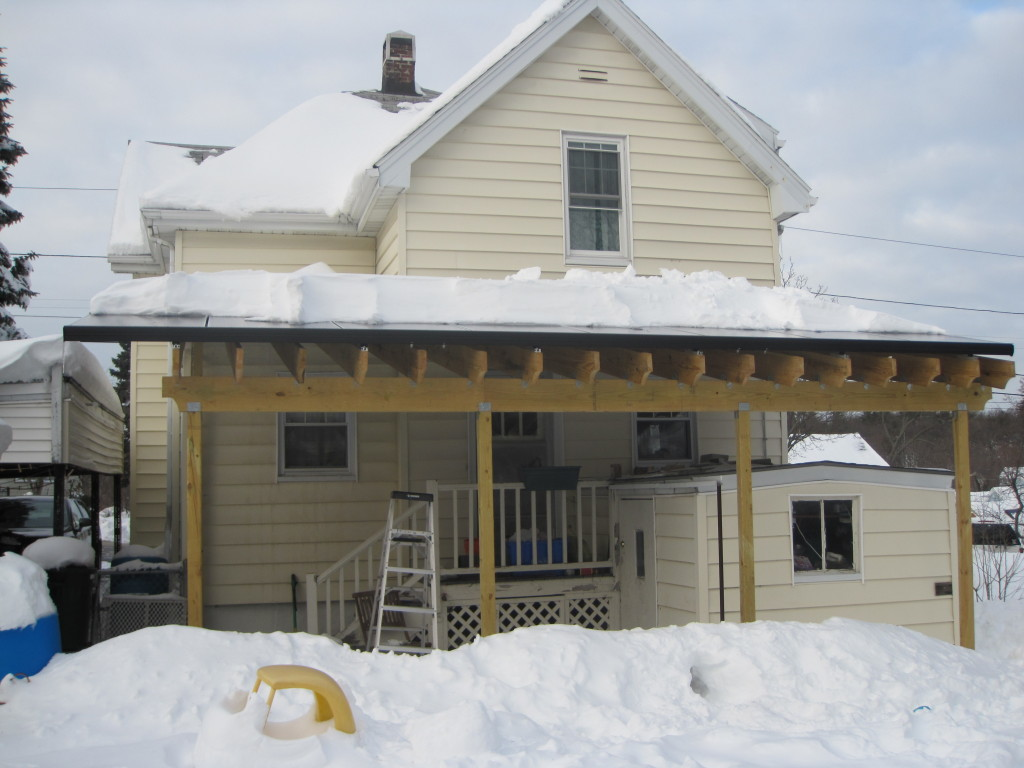 back of house with solar awning covered in snow