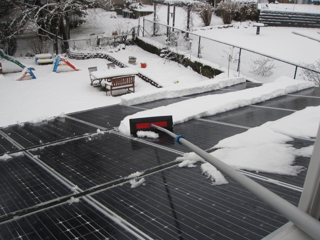 Using a pole to carefully remove snow from solar panels