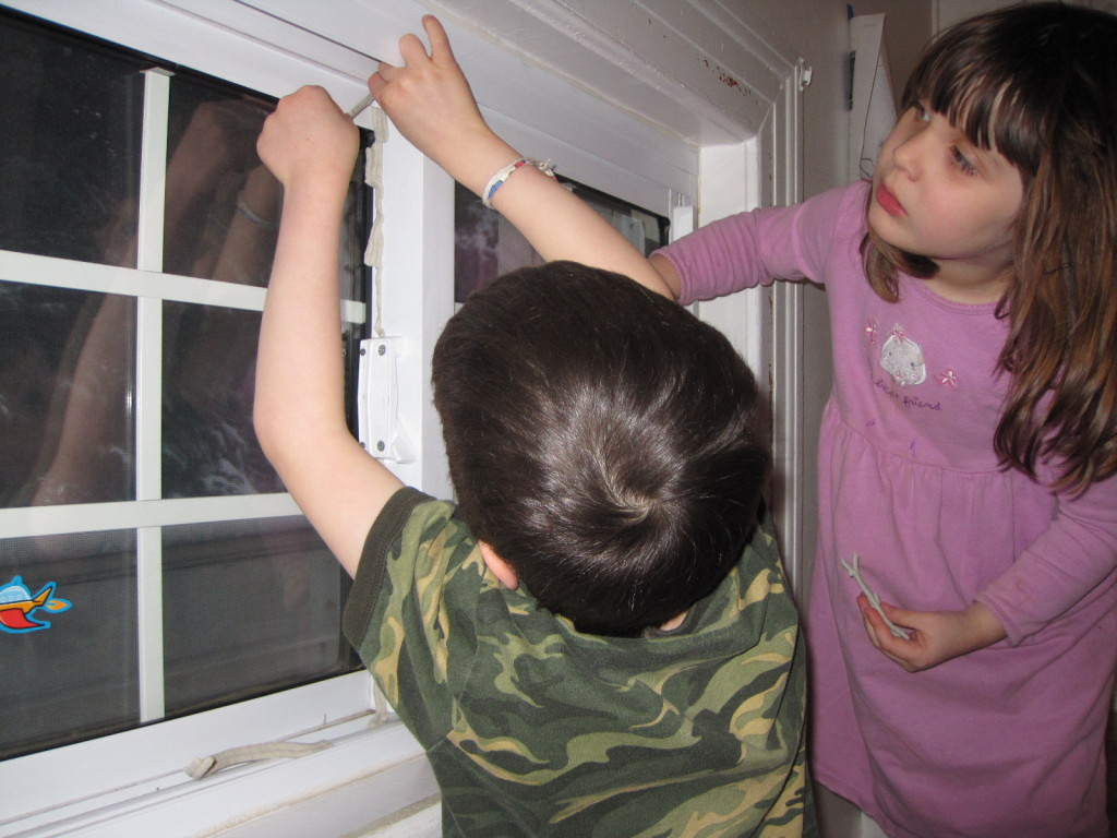 Children putting mortite on a window
