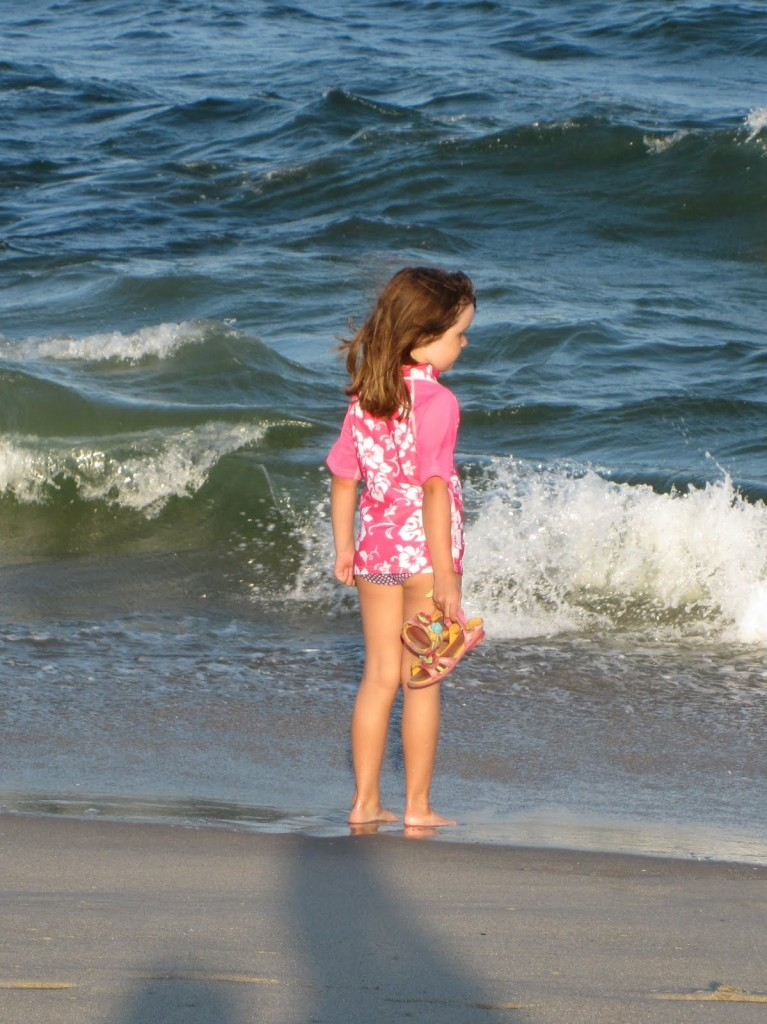 young girl at beach wearing a swim shirt for protection from the sun