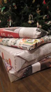 stack of presents under a tree wrapped in newsprint