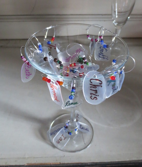martini glass with a bunch of personalized wine charms