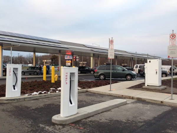 2 Tesla Super Charging hookups at a rest area with the gas pumps in the background and solar panels above the pumpsBest 2 parking spaces at Milford, CT rest area reserved for Tesla Super Charging Stations