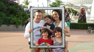Hunt family holding picture frame at Epcot