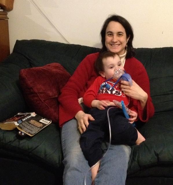 child sitting on mom's lap using nebulizer
