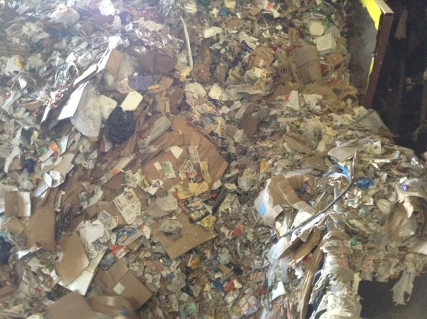 A close-up of the material on the floor of the recycling facility about to go up the conveyor belt.