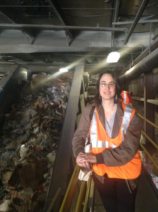 Alicia at the start of the recycle stream. This conveyor belt is taking recycling off the plant floor and starting to get it into a layer thin enough for the other equipment to work with.