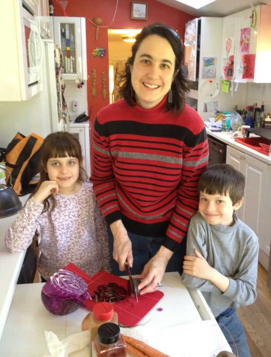 Alicia with Ellie & Christor cutting up beets and purple cabbage to dye Easter Eggs.