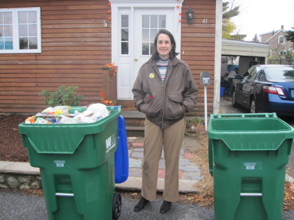 Alicia standing between two large green toters, the big one is for recycling.