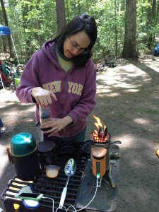 Alicia pressing aeropress coffee maker with BioLite Camp Stove charging iPhone