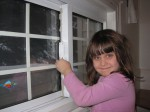 Young girl applying air sealing film to a window
