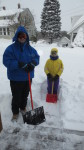 Father and daughter standing in snow gear with snow shovels
