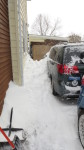Snow piled over the hood of the minivan between the car and the house