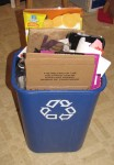 blue recycling bin overflowing with boxes and papers